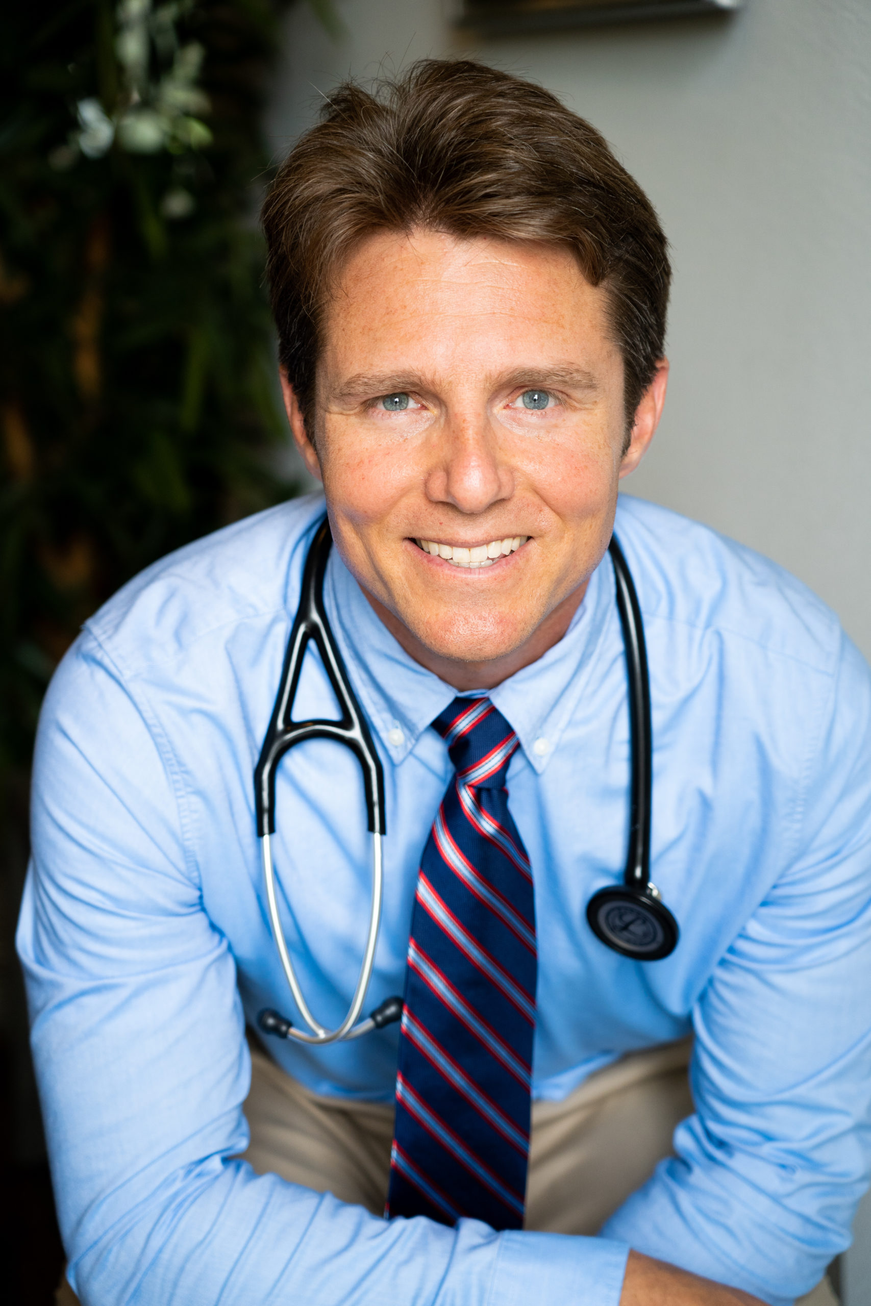 A closeup of Dr. Scott Harrington DO, a vegan doctor, a Plant Based Family Medicine Doctor, it is a head shot and he is wearing a blue shirt with a blue and red tie. He is wearing a stethoscope.
