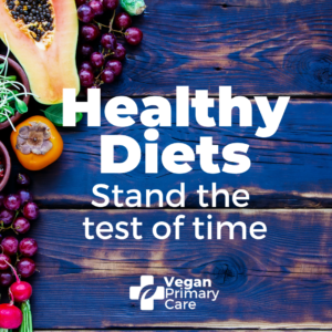 "Photo showing healthy fruit and vegetables on a rustic wooden tabletop with the words ""healthy Diets stand the test of time"" and below is the logo for veganprimarycare.com"
