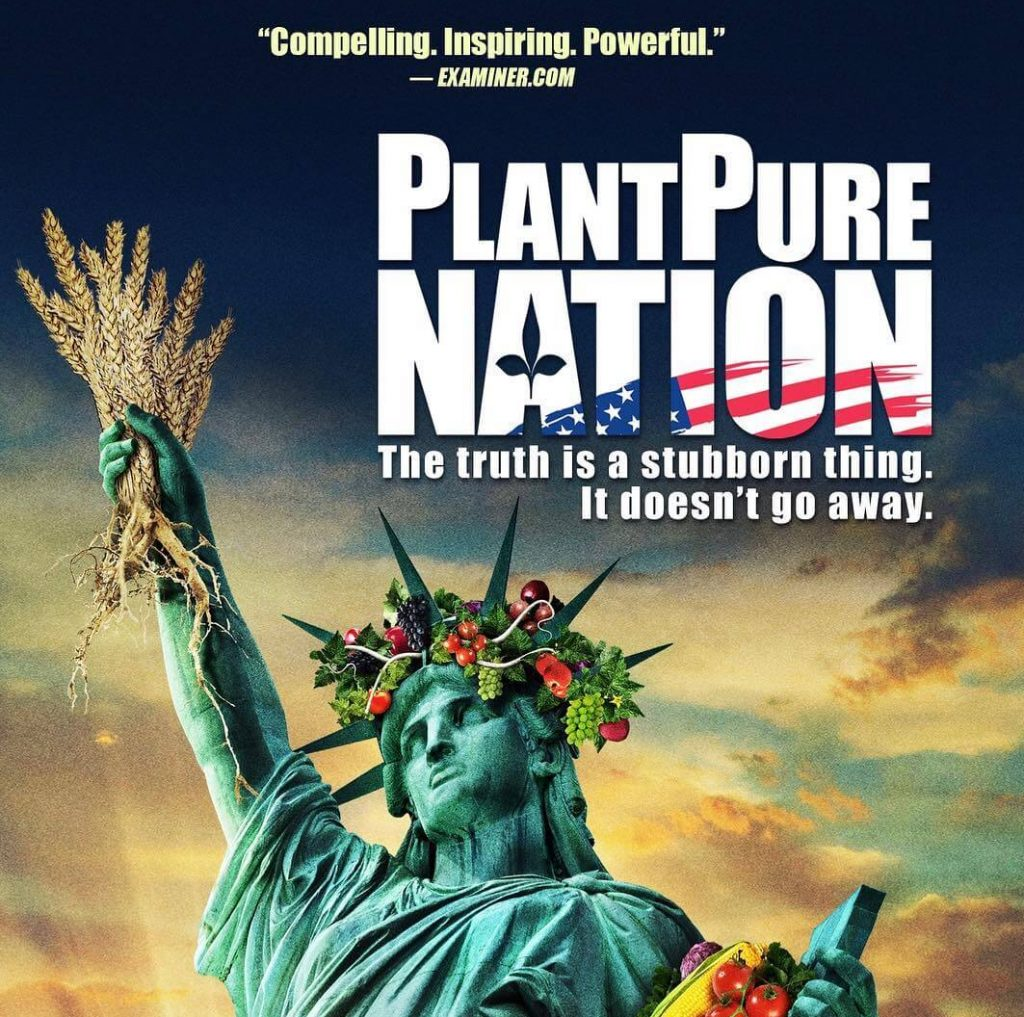 A vegan Movie poster for PlantPure Nation showing a statue of liberty holding grain instead of a torch and she is adorned with fruits and flowers