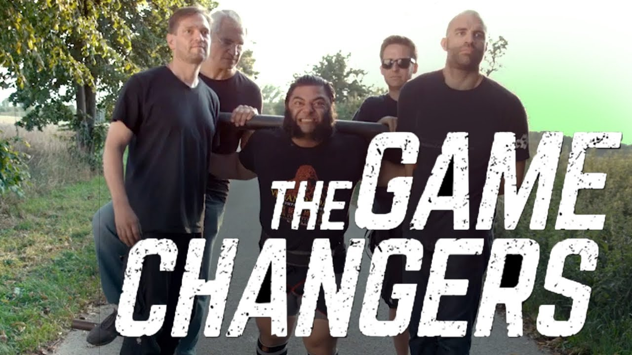 Movie poster with a vegan strongman lifting 4 men on a sled with the words the game changers